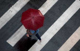 Weber Sian / A Cidade - Mulher caminha em meio a chuva em Ribeirão Preto