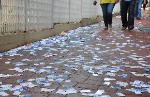 Tiago de Brino / A Cidade - Casal caminha sobre santinhos espalhados por calçada de Ribeirão Preto