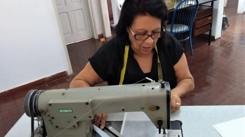 A voluntária Lucia Chaves costurando os equipamentos de proteção individual  Foto: Divulgação - Foto: Divulgação