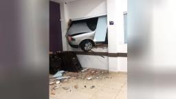 Motorista bate carro que fica pendurado em janela de comércio